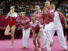 Russian gymnasts and team officials react as teammate Kseniia Afanaseva falls while performing on the floor during the gymnastics women's team final.
