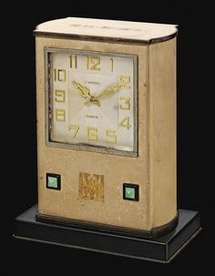HARD STONE, TURQUOISE AND ENAMEL DESK CLOCK, CARTIER, CIRCA 1934.  Of rectangular form, the square dial applied with Arabic numerals, the beige enamel case decorated with turquoise and black enamel geometric elements, to the yellow gold initials VW  inset to the front and, 20-2-34 inset to the top, dial signed Cartier Paris, the base signed Cartier and numbered.