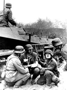 German Wehrmacht soldiers take cover behind an Sd.Kfz. 250 (German: Sonderkraftfahrzeug 250; 'special motor vehicle') light armored halftrack to tend to a wounded comrade during the First battle of Kiev during Operation Barbarossa; the German...