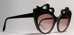 Vintage eyewear. Vintage sunglasses. Cat eye style. Made in France. 1970s. Mod! Stunning gloss black. The scroll cut out design along brow line is very unique and rare to find. A white stripe follows along the top of the scroll design. Frame is high quality and in excellent condition. All authentic original frame and tinted lenses. Wear as is or frame is ready for your prescription or non-prescription lenses. Eye size 55mm. Bridge size 15mm. Temple length 140mm. Measurement across frame…