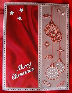 A simple, yet pretty, red and white Christmas card using Pergamano rub-ons for the stars, holly, and baubles, with a grid design enhancing two of the baubles.