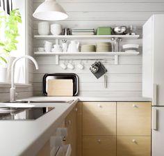 Benkeplater i laminat med oppvaskkum i rustfritt stål og hvite vegghyller i bakgrunnen
