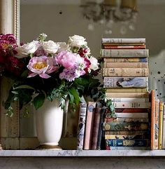 Flowers in a white vase, books with paper jackets, a mantle, a mirror, and a chandelier -- oh, my!