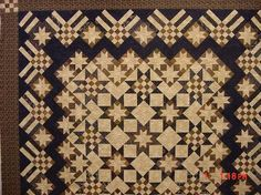"Viewer Photo of a Stars and Stripes Forever, designed by Judy Martin for her book, Knockout Blocks & Sampler Quilts. Instead of plain edge triangles around the diagonally set blocks, Judy used units of 2 small stars and a triangle in the corners; she used units of 3 stars and a triangle along the sides. This makes the appearance of an inner border, and with the dark triangles  repeated in the pieced outer border, a dark zigzag ""border is formed. The outer border is pieced from 3 block types."