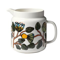 Marimekko's Tiara pitcher features rich botanical motifs, designed by Erja Hirvi. The charming pattern is composed of orange undulating branches filled with exotic fruits and flowers.
