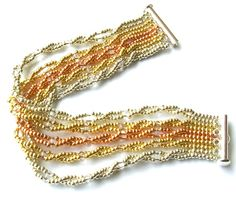 Bracelets - Gemini Strands starts and ends with a length of flat Ndebele and has five twisted strands of size 11° seed beads and twin beads stretched between them