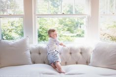 Toddler playing on a white couch in front of a wall of windows. Naturally styled portrait by N. Lalor Photography.