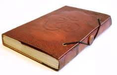 A Unique hand made recycled paper journal or sketch book from India. This piece has beautiful imprint of the mantra OM on the leather cover and patterns in the front and back of the book.