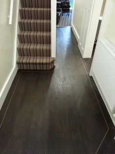 dark solid wood floor, near white walls and door, hallway decorating ideas, narrow staircase, covered with striped rug, in different shades of brown
