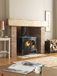 Earthy tones, red brick, wood mantel and a traditional stove. Sometimes you can't beat the classics. Earthy tones, red brick, wood mantel and a traditional stove. Home, Wood Stove Surround, Wood Burner Fireplace, New Homes, Wood Mantels, Brick Fireplace, Wood Burning Stove, Fireplace, Fireplace Hearth