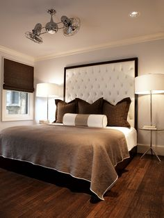 This guest bedroom is soothing and modern. The high-tufted headboard, designed by Pulp Design Studios, creates drama in the space. The tall headboard is grounded by custom windows and bedding. Home Bedroom, Bedroom Decor, Bedroom Ideas, Bedroom Ceiling, Design Bedroom, Bedroom Photos, Bedroom Lighting, Bedroom Chandeliers, Warm Bedroom