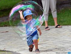 UKRAINE, Kiev: A boy plays with a soap bubble in one of Kiev parks on a hot day in the Ukrainian capital on July 5, 2013. AFP PHOTO / SERGEI SUPINSKY