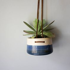Use this hand-built stoneware hanging wall planter to elevate your plants and add a bit of nature to any space. This modern hanging wall planter is perfect for succulents, cactus, or other plants. The planter is wheel thrown and glazed in a white and blue glazes. The natural