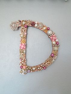 """D"" made using vintage jewelry. Spray painted wooden letter copper. Gathered various pieces of vintage jewelry (earrings missing their mate, broken pieces, pieces ""repaired"" by gluing rhinestones/beads/etc. over defective areas, etc.). Use tin snips to remove backings/cut to desired size. Then hot glue to the wooden letter."