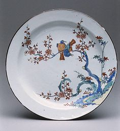 Dish with flowers and birds, 18th century. Chinese with Dutch decoration. A Japanese Kakiemon-style bird-and-flower painting has been used here by a Dutch painter to decorate a Chinese porcelain blank.