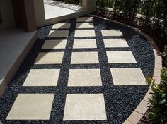 Polished Black River Rock With Stone Square Walkway With Stone Border In The Beside Home With Small Trees