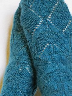 top-down sock pattern features a geometric, lacy design that combines a variety of textures and simple cables to create a complicated-looking sock that actually works up quickly while keeping your attention the whole way down. Pattern includes both charted and written instructions.