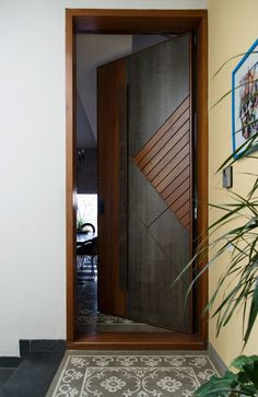 A subtle yellow wall leads to the main door of the house finished in stone and wood while the patterned tiles act as a faux rug. Photography by Prachi Damle Source by bhomesindia Modern Entrance Door, Main Entrance Door Design, Wooden Front Door Design, Modern Wooden Doors, Door Gate Design, Wooden Front Doors, Modern Door, Internal Doors Modern, House Main Door Design