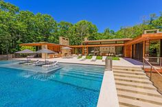 Walls of windows let in the gorgeous scenery surrounding this Amagansett, New York, home. The ranch-style house features an open floor plan and a midcentury-modern decor style. An infinity-edge swimming pool is surrounded by trees for enjoying total privacy in the great outdoors.