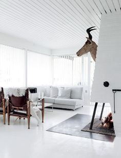 White living space with leather armchairs and painted ceiling