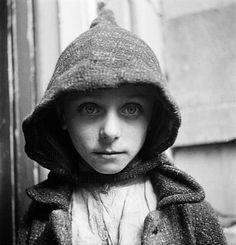 © Cas Oorthuys. Schaars geklede jongen voor een deur op straat in de hongerwinter, Amsterdam, 1944 - 45. Nederlands Fotomuseum, Rotterdam