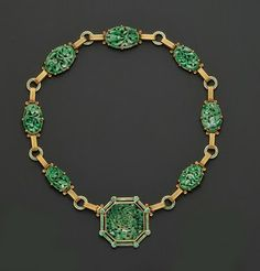 made by Tiffany & Co in the 1930's that displays seven oval carved jadeite plaques set in yellow gold and enamelled links with an octagonal carved jadeite pendant. It is probably one of the few Art Deco pieces in yellow gold