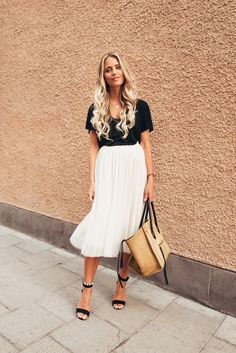 A white flowing pleated skirt like this one is the perfect way to wear this summer's hottest trend! Janni Deler is looking totally striking in this gorgeously contrasting outfit consisting of a white skirt, a black top and sleek black heels. Shirt:...