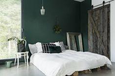 """Makuuhuoneessa on käynyt jo useampi sänky. Toistaiseksi mukavin on kasattu kuormalavoista. Vihreä seinä on maalattu Tikkurilan vuoden värillä """"Vuono"""". Elina osti makuuhuoneen peilin heti, kun talolle tuli rakennuslupa. Jännä liukuovi piilottaa vielä keskeneräisen kylpyhuoneen."""