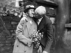 76-year-old Evan Ellis of Anglesey kissing his bride, 70-year-old Mary Ann Kinsley after their wedding at Ton Pentre, Rhondda. July 1936.