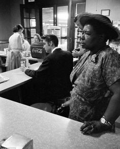 Elvis Presley waiting for his bacon and eggs while a woman waits for her sandwich. she is not permitted to sit, 1956.