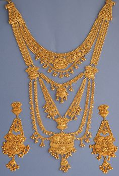 Gold Ranihaar set The Ranihaar set is normally worn by the bride on the wedding day. The long necklace decorates the neck to the stomach. The top part of the necklace is detachable whereby it can be worn by itself. Dubai Gold Jewelry, Gold Jewellery Design, Pearl Bridal Jewelry Sets, Gold Initial Pendant, Gold Earrings Designs, Gold Fashion, Jewelry Patterns, Indian Jewelry, Chandelier Earrings