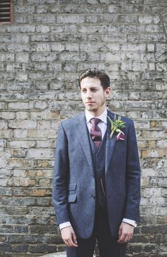 Groom wears a three piece suit and brown tie | Photography by http://heartsonfire.co/