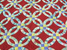 Double wedding ring quilt. Patchwork on red background.