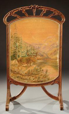 LOUIS MAJORELLE walnut fireguard carved with floral and plant motifs, holding a velveteen painting of an elk calling in a mountain landscape. Circa 1900. H : 46 in
