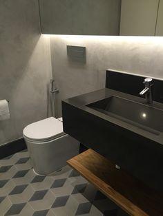 Lavabo: piso em ladrilho hidráulico hexagonal, bancada  com cuba esculpida em granito cinza absoluto, paredes em tecnocimento e espelho retroiluminado.