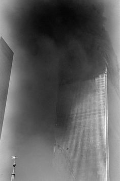 *9/11~I SAW A LOT OF PEOPLE JUMPING:  I couldn't take pictures of that. I couldn't believe my eyes, that people had the strength, to die this way.To me it was the most powerful moment because a year before this I went on top of the WorldTradeCenter for the first time, I remember what I felt looking down, how high + scary it was.Seeing these people, I was picturing them looking down.You can see two silhouetts of people jumping from the building. I didn't know until I saw it on my print.