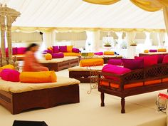 Indian Style dark wood sofas with color coordinated pillows for seating in wedding party tent.