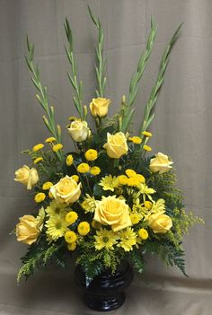 Rays of Light- yellow standard roses, yellow chrysanthemum daisies, yellow button mum daisies, yellow solidago, yellow gladiolas and leather fern in a black urn container