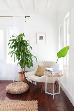 A cozy bohemian living room corner with a midcentury upholstered arm chair draped with a tasseled throw, contemporary three-leg side table, woven water hyacinth sea grass floor pouf cushion and potted plant for a pop of color!
