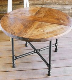 "Reclaimed wood is pieced into a round shape with a crossed ""x"" pattern and stained a light honey brown hue. The tabletop is perched on grey powdercoated pipe legs for industrial flair."