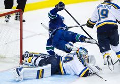 Vancouver Canucks' Dan Hamhuis, top, trips over St. Louis Blues' goalie Jake Allen during the third period of an NHL hockey game in Vancouver, B.C., on Friday, Oct. 16, 2015.