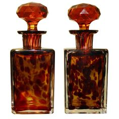 A pair of turn-of-the century handblown tortoise glass perfume bottles with faceted stoppers.