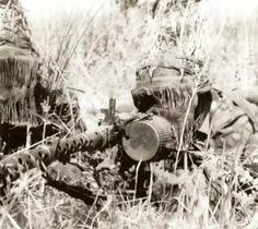 Пулеметный расчет с пулеметом МГ-34. Эсэсовцы хорошо замаскировались не только естественным камуфляжем, но штатными камуфлированными масками для лица М42.