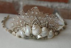 What about a paper-doily crown painted blue marble and add shells? Items similar to Seashell and Coral Crown Tiara w/ Rhinestone Bling for Beach Wedding Prom Sweet 16 on Etsy