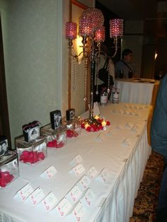 wedding idea-Card table-Instead of picture frames, we had blocks made with our pictures on them and the blocks spelled out LOVE. They were placed on clear blocks with rose petals inside. They matched our table number theme-every table was love in a different language. They were black and white with one hot pink ribbon on one block to match our hot pink, black and white theme. We also had one tall centerpiece on the table.