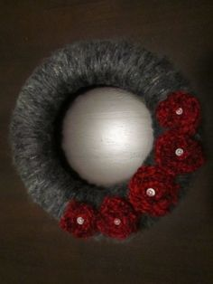 Fuzzy grey and crimson yarn wreath. This would look a bit brighter if I changed the grey yarn to green...