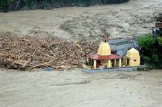 In this handout photograph released by The Indian Army on June 18, 2013, debris carried by floodwaters of the River Alaknanda crashes against a Hindu Temple in Chamoli district in the northern Indian state of Uttarakhand on June 18, 2013. Posted by floodlist.com #floods #uttarakhand
