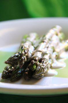Alcuni asparagi su un piatto, cosparsi con besciamella crudista