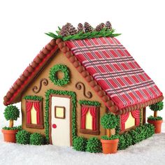 This gingerbread house would be perfect for a rustic rendezvous! The plaid iced roof and realistic pine cone trims let you show off your decorating skills.