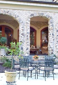 Country French home loggia.  Leo Dowell Designs surrounded these arches with rubble stone to add a vintage feel.